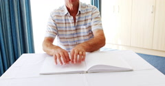 Senior man reading a braille book Stock Footage