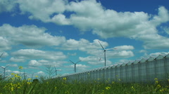 A meadow with a greenhouse and a wind turbine Stock Footage