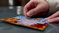 Scratching lottery ticket inside shopping mall Stock Footage