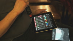 Man adjusts sound equipment using a digital tablet Stock Footage