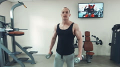 Strong sportsman carrying dumbbells Stock Footage