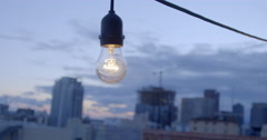 Light bulb hanging in front of Downtown Los Angeles skyline at sunset 4K Stock Footage