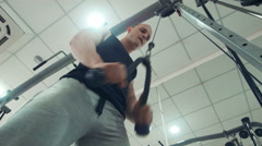 Sportsman doing exercise on triceps with rope - stock footage