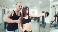 Long-haired sportswoman and tattooed sportsman taking selfie in gym - stock footage