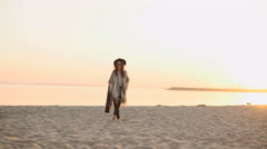 Woman back walking on the beach with guitar - stock footage