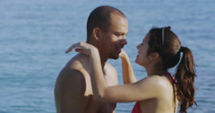 4K Happy attractive couple at the beach share a kiss as they stand in the water - stock footage