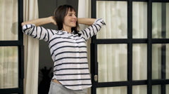Young woman unveil curtains and stretching arms standing in room door Stock Footage