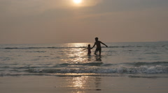 Father playing with his children from sea on sunset background, - stock footage