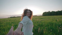 The romantic concept of young beautiful girl holding hand running in a field - stock footage