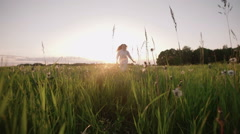 Young beautiful girl running in a field,sunset, slomotion Stock Footage