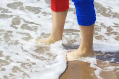 Beautiful woman legs with tucked up trousers  walking on a beach - stock photo