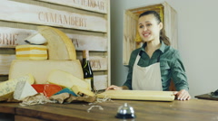 The buyer buys a piece of cheese, to pay for goods in cash. Buyer's seen from - stock footage