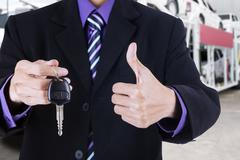 Businessman shows OK sign and a car key - stock photo