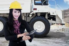 Businesswoman and a mining truck at mining site - stock photo