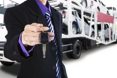 Driver giving a car key with trailer truck background Stock Photos