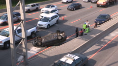 Firefighters police at car rolled over accident scene on highway Stock Footage