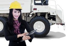 Female worker and a mining truck - stock photo