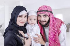 Happy Arabic parents and their child at home - stock photo