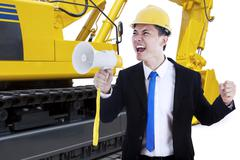 Male contractor with megaphone and excavator - stock photo