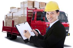 Male worker with clipboard and logistic truck - stock photo