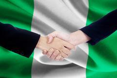 Partnership handshake with flag of Nigeria Kuvituskuvat