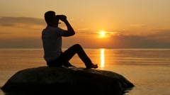 Mans silhouette with binoculars on small island smooth follow focus Stock Footage