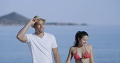 4K Happy attractive couple holding hands as they walk along the beach Stock Footage