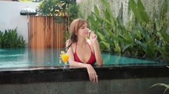 Woman in red swimsuit relaxing in swimming pool with juice and smells frangipani - stock footage