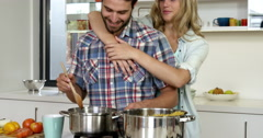 Cute girl hugging his boyfriend while he is cooking Stock Footage