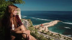 Young woman sitting on the edge of a cliff overlooking roads and ocean Stock Footage