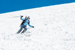 Female skier tackling a steep slope. - stock photo