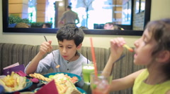 Children, brother and sister eating sandwiches in the cafe. french fries Stock Footage