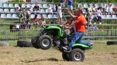 Man rides an ATV motor on a car derby show entertain public with stunt tricks - stock footage