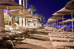 Sunbeds and umbrellas on the beach in the evening Stock Photos