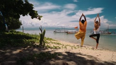 Man and woman doing yoga on a beach in Sanur, Bali Stock Footage