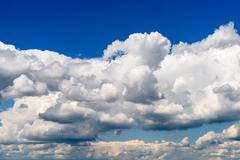 White Cumulus Clouds And Grey Storm Clouds Gathering On Blue Sky - stock photo