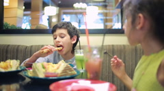 Children, brother and sister eating sandwiches in the cafe. french fries. family Stock Footage