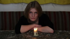 Depression. Young sad woman sitting with a candle on the table, gloomily look - stock footage