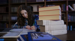 Student overlaid with books around and writing in a notebook. 4K - stock footage