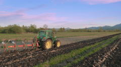 Aerial: Farmer Plowing a Field with a Beautiful Countryside in Background Stock Footage