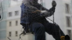 A man hanging on a wall and washing window. Blurred veiw through the glass Stock Footage