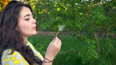 Curly hair woman in the Park blowing on a dandelion. Slow motion - stock footage