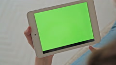 Back view of woman at home using and scrolling electronic tablet, green screen Stock Footage