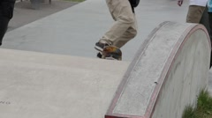 Skateboarder sliding on a ledge in skate park Stock Footage