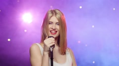 Blonde girl singing into a retro microphone, strobe lighting effect Stock Footage
