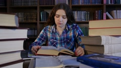 A tired student is preparing for exams in the library. 4K - stock footage