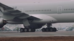 Wheels and turbines of an 777 300ER boeing moving on a runway in the airport Stock Footage