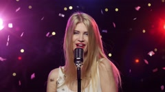 Blonde girl singing into a retro microphone strobe lighting effect Stock Footage
