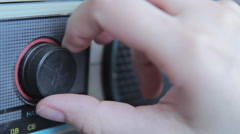 Closeup of hand turning a volume control on an old radio Stock Footage