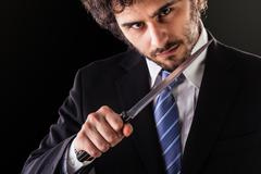 Murder businessman with kitchen knife Stock Photos